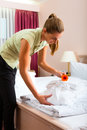 Maid doing room service in hotel she is making up the beds Stock Images