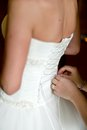 Maid of honor helping the bride to put her wedding dress honorhelping on by tying back bow or lace Stock Photos