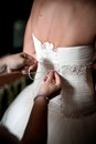 Maid of honor helping the bride to tie the wedding dress put her on by tying back bow lace up s Royalty Free Stock Photo
