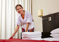 Maid in hotel room making bed housekeeping Stock Image