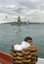 Maiden tower a young salesman simit bread vendor istanbul turkey december european part of istanbul in the background against the Royalty Free Stock Photography