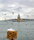 Maiden tower a young salesman x simit x bread vendor european part of istanbul in the background against the shore left blue Stock Images