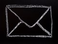 Mail symbol drawn on blackboard with white chalk Stock Images