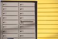 Mailbox Rows and Wall With Yellow Siding Stock Images