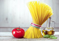Main ingredients for traditional italian pasta close up of the raw spaghetti a tomato aromatic basil leaves and olive oil Royalty Free Stock Image