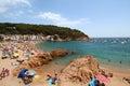 Main view of crowdy beach of Tamariu with village in background, Costa Brava, Catalonia, Spain