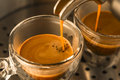 Mainstream of strong espresso coffee from a machine to translucent glass cups Stock Image