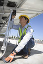 Maintenance worker installing solar photovoltaic panels young on rooftop Royalty Free Stock Image