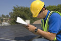 Maintenance worker making notes near solar panels side view of young on rooftop Stock Images