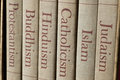 Major world religions book spines listing judaism islam catholicism hinduism buddhism and protestantism Royalty Free Stock Photo