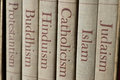 Major world religions book spines listing judaism islam catholicism hinduism buddhism and protestantism the focus is on the word Stock Images