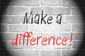 Make a difference text written in black and red on black and white brick wall with vignetting Royalty Free Stock Photography