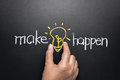 Make idea happen concept hand taking light bulb between words written by chalk Stock Images