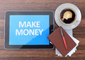 Make money online on tablet pc computer with cup of coffee, notebook and pen on wooden background Royalty Free Stock Photo
