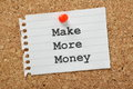 Make more money the phrase typed on a piece of note paper and pinned to a cork notice board Stock Photos