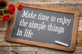 Make time to enjoy simple things the inspirational advice white chalk text on a vintage slate blackboard with red roses against Stock Photo