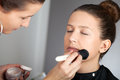 Make up artist applying powder on models face Royalty Free Stock Images
