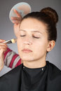Make up artist applying powder on models face Royalty Free Stock Photo