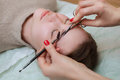 The make-up artist combs and shear her brows with scissors to a beautiful young girl Royalty Free Stock Photo