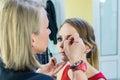 Make-up artist doing smoky eyes makeup to beautiful young girl