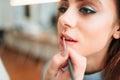 Make up artist hand applying gloss on woman lips Royalty Free Stock Photo
