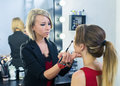 Make-up artist preparing for makeup to beautiful young girl