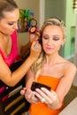 Make up artist at work applying make up on beautiful blond girl Stock Image