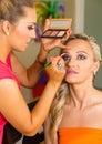 Make up artist at work applying make up on beautiful blond girl Royalty Free Stock Photo