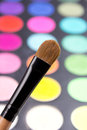 Make up brush and colorful eyeshadow palette close up over black Stock Image