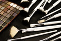 Make up brushes in dark background and eye shadows Royalty Free Stock Images
