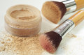 Make up mineral powder in plastic jar with cosmetic brushes Royalty Free Stock Photo