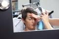Make up model at mirror in dressing room, sprays hair spray