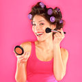Make up woman putting makeup blush getting ready for fun funny beautiful young female model with hair rollers in pink dress on Royalty Free Stock Image