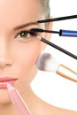 Makeover beauty transformation concept with makeup face asian woman many brushes against one side of the face putting mascara Stock Photo