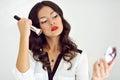 Makeup applying beautiful girl with cosmetic powder brush Stock Photos