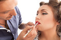 Makeup applying make up artist applying lipgloss Royalty Free Stock Images