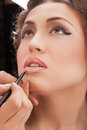 Makeup applying make up artist applying lipgloss Stock Photo
