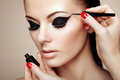Makeup artist applies eye shadow Royalty Free Stock Photo