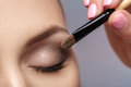 Makeup artist apply makeup brush for eyes. makeup for young girl. brown eye shadow. close up Royalty Free Stock Photo