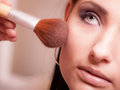 Makeup artist applying with brush powder rouge on female check Royalty Free Stock Photo