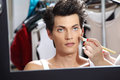 Makeup artist applying foundation with a brush, man in the dressing room mirror Royalty Free Stock Photo