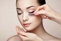 Makeup artist glues eyelashes beautiful woman face perfect beauty fashion cosmetic eyeshadow Royalty Free Stock Photo