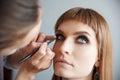 Makeup artist glues false eyelashes to young beautiful woman Royalty Free Stock Photos