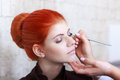 Makeup artist preparing redhead model Stock Photo