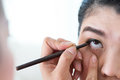 Makeup beauty with brush eye liner on pretty woman face Stock Image