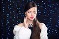 Makeup beauty fashion model girl in white mink fur coat elegan elegant brunette woman posing over blue holiday lights background Stock Image
