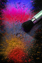 Makeup brush with holi paint covered bright dry powder Royalty Free Stock Photo