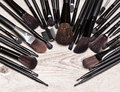 Makeup brushes arranged in semicircle on shabby wooden surface various professional tools of make up artist round frame with small Royalty Free Stock Images