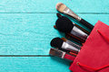 Makeup brushes on blue wooden background with copyspace. Make-up tools in red paper bag. Top view Royalty Free Stock Photo