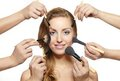Makeup brushes near attractive face many hands Stock Photo